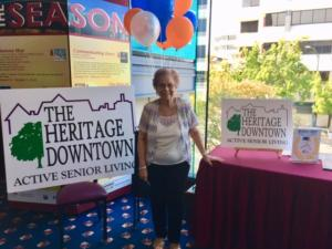 Image of a Heritage Downtown resident with sign at a community event