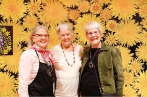 3 beautiful residents in front of a wall of sunflowers